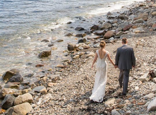 A bride and groom walk near the shore