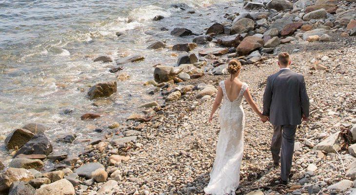 A bride and groom walk near the shore