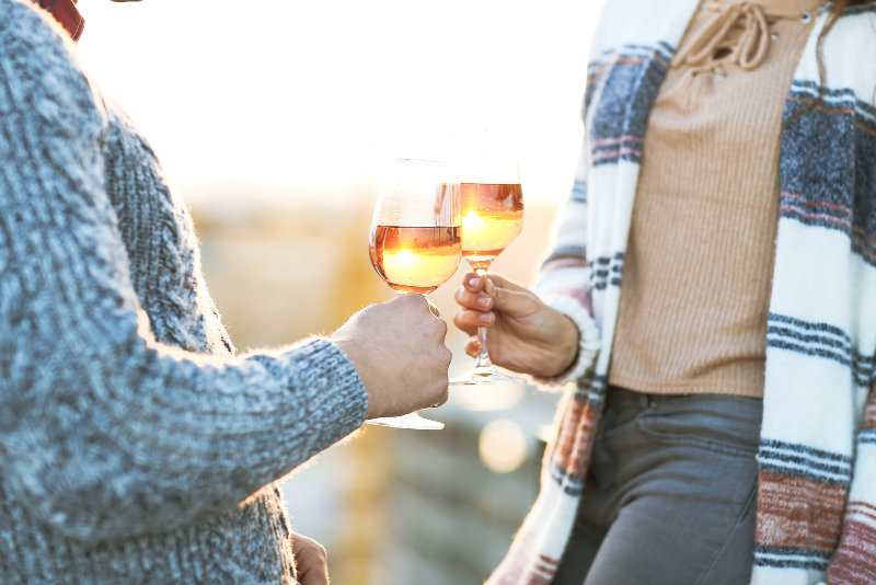 Couple toasting with wine outside