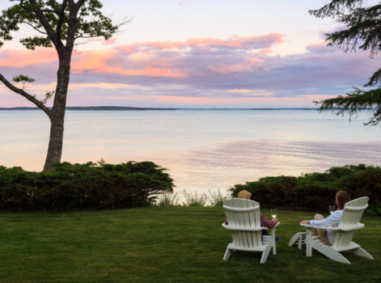 Couple in Adirondack chairs relaxing with wine