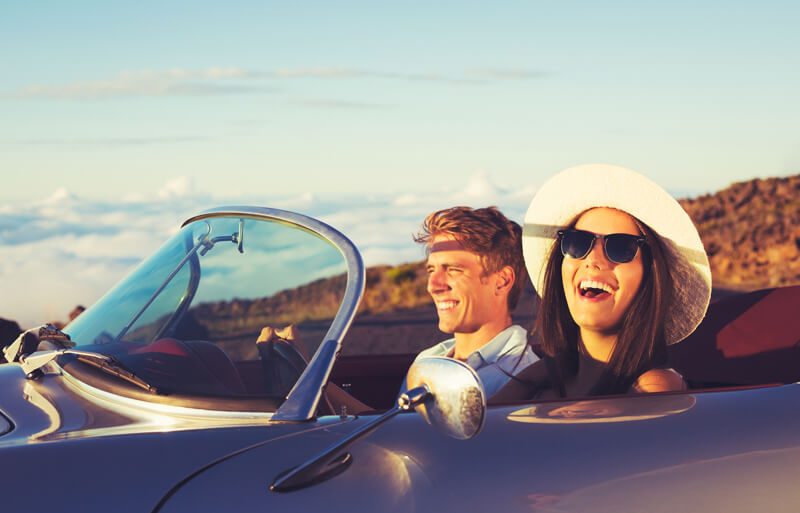 happy couple driving in convertible with the coast in the background
