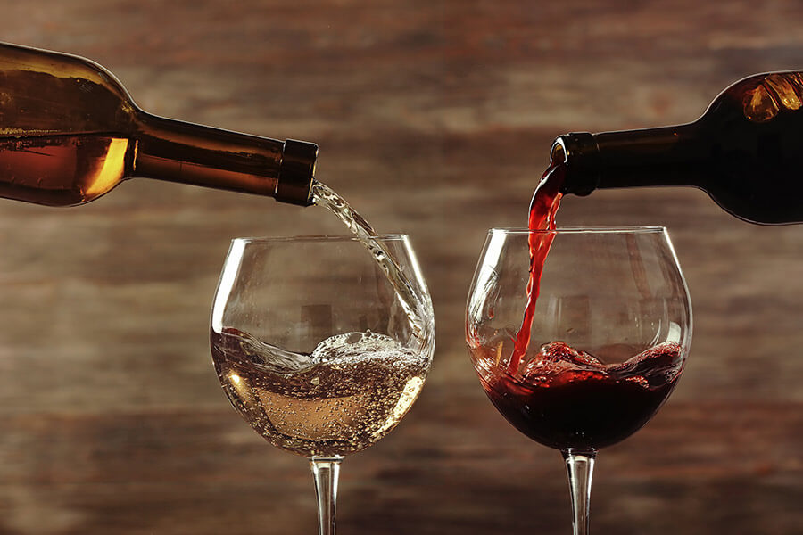 pouring red and white wine into glasses